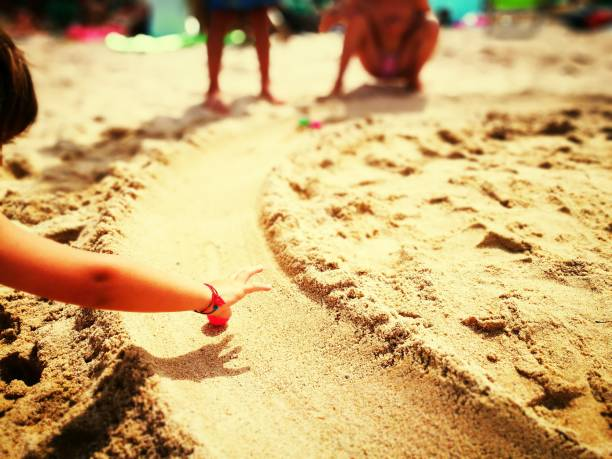 Children Playing In Sand At Beach