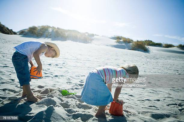 children playing in sand - bending over in skirt stock pictures, royalty-free photos & images