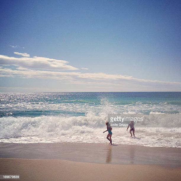 children playing in the ocean on hot day at beach - middlebare afstand stockfoto's en -beelden
