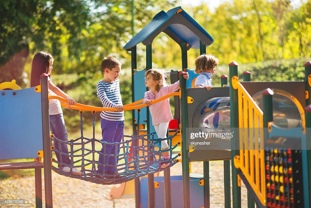 Children playing in the park at playground and communicating. : Stock Photo