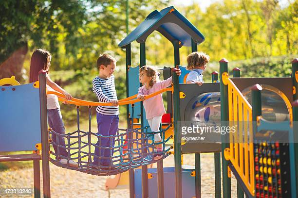 Children playing in the park at playground and communicating.
