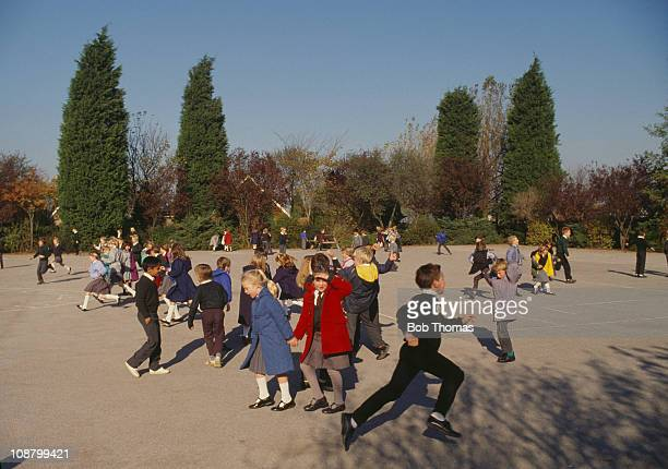 Children playing in the playground at their school Northamptonshire 1988