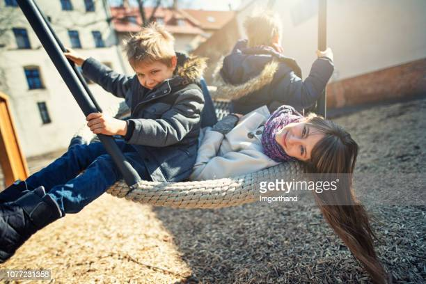 children playing in the playground during winter - imgorthand stock photos and pictures