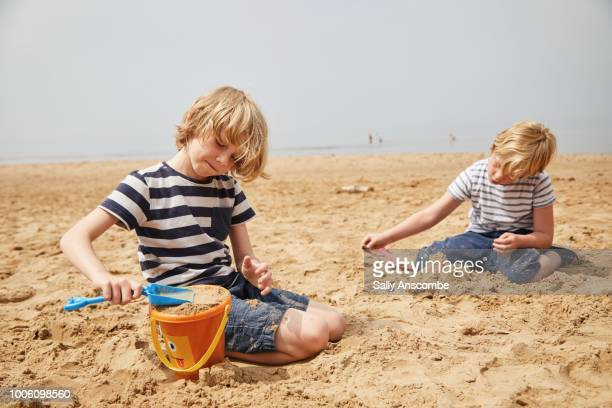 children playing in the sand - children only stock pictures, royalty-free photos & images