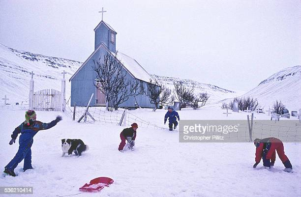 Children playing in the snow on ther farm near the village of Sudureyri Iceland