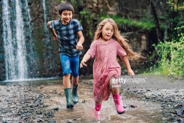 Kinder spielen im Wasser in der Nähe eines Wasserfalls