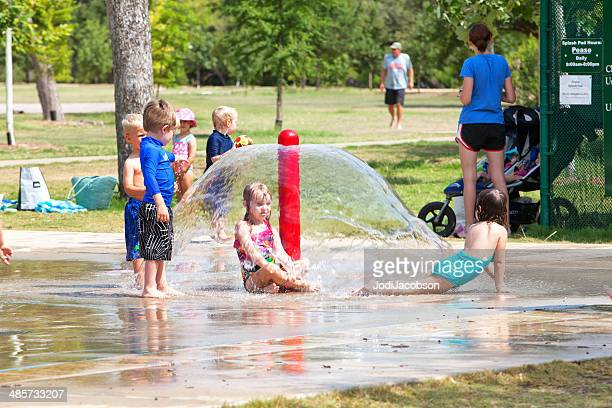 Children playing in water spouts