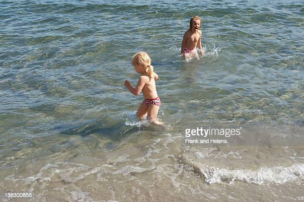 Kinder in Wellen am Strand