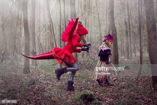 Children playing in witch and dragon costume in the woods