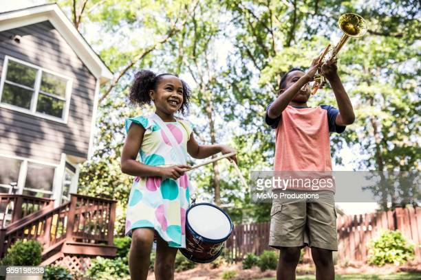 children playing instruments and marching outdoors