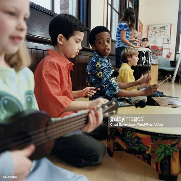 Children (8-10) playing instruments in classroom