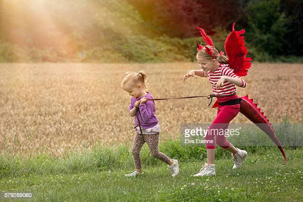 children playing make believe with pet dragon - zakelijke kleding stock pictures, royalty-free photos & images