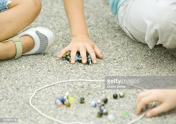Children playing marbles on asphalt