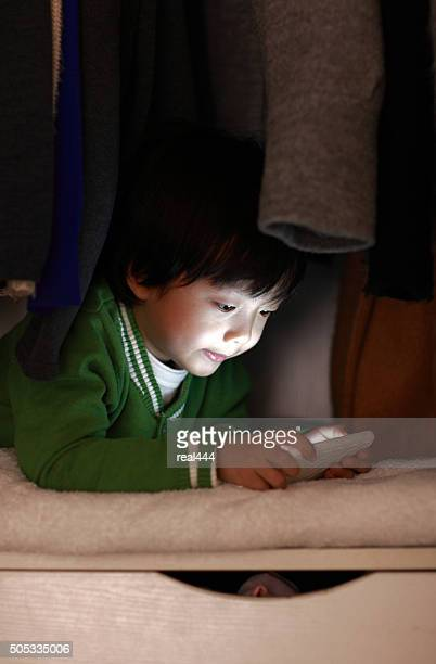 Children playing mobile phones in the closet