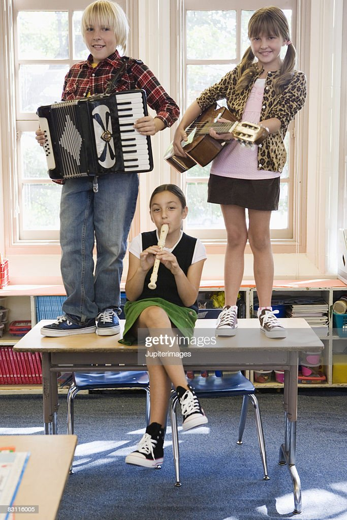 Children playing musical instruments in classroom : Stock Photo