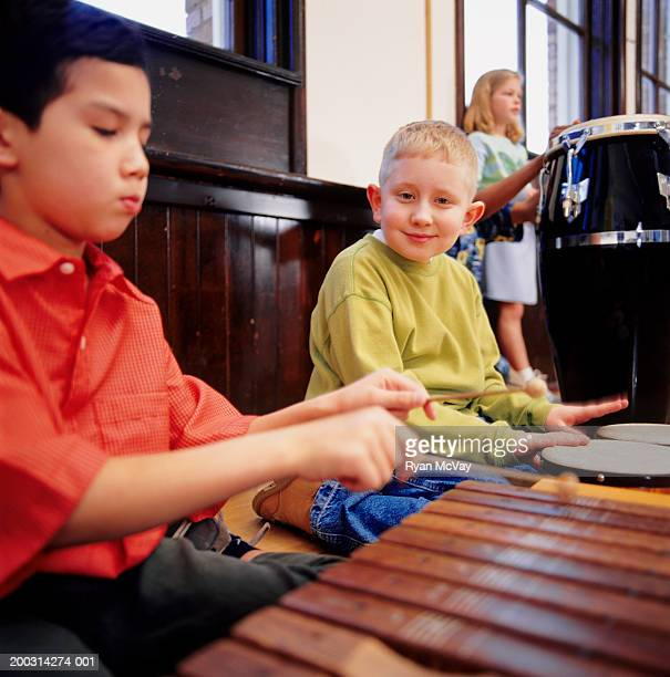 children (8-9), playing musical instruments in school, portrait - percussion mallet stock pictures, royalty-free photos & images