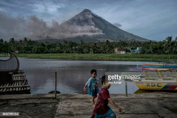Children playing near a lake as Mayon volcano spews ash and lava on January 17 2018 in Camalig Albay Philippines Thousands evacuate as Philippines'...