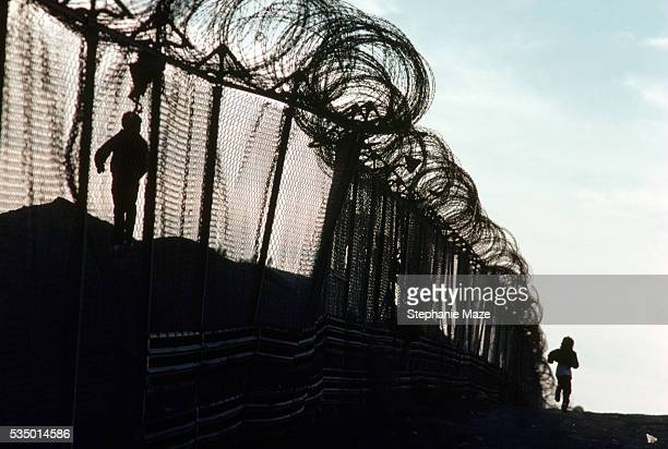 Children Playing Near Barbed Wire Border Fence