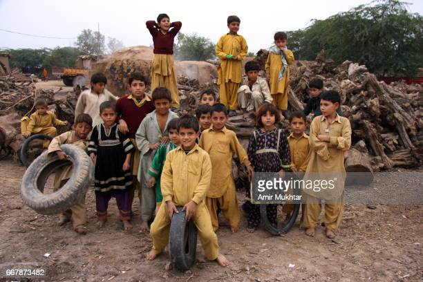 children playing near charcoal making oven - pathan girls stock photos and pictures
