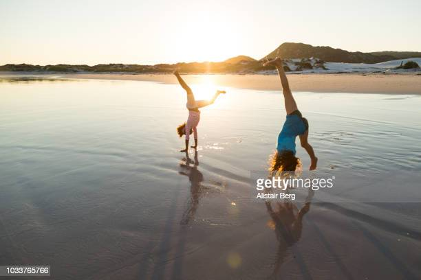 children playing on a beach at sunset - cartwheel stock pictures, royalty-free photos & images