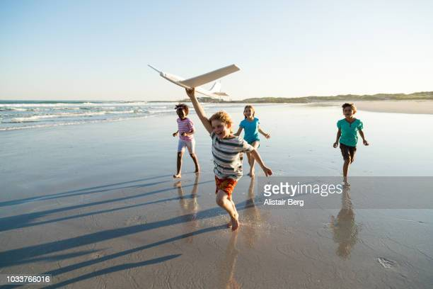 children playing on a beach at sunset - jugar fotografías e imágenes de stock