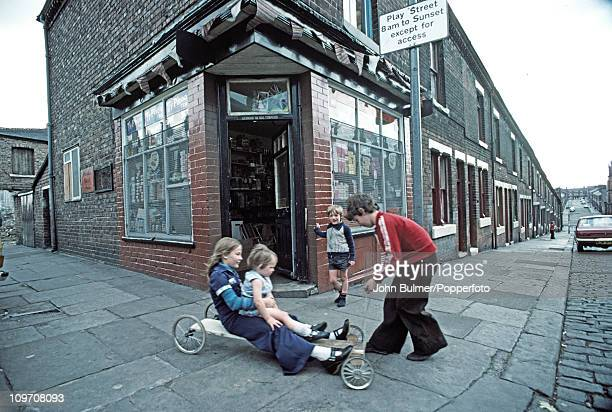 Children playing on a homemade gocart outside a corner shop in Manchester 1976 Above them is a traffic sign designating a play street