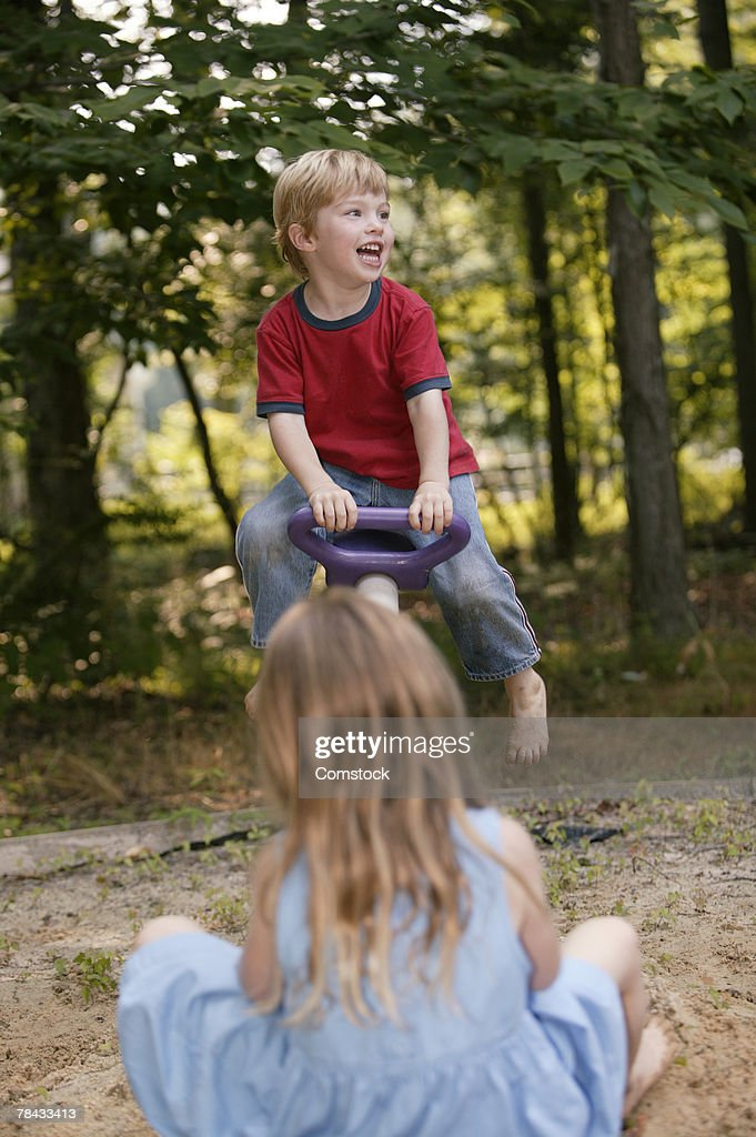 Children playing on a seesaw : Stockfoto