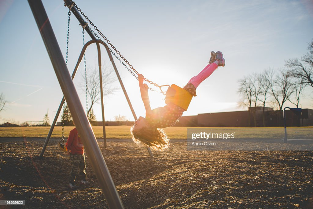 Children playing on a swing set : Stock Photo
