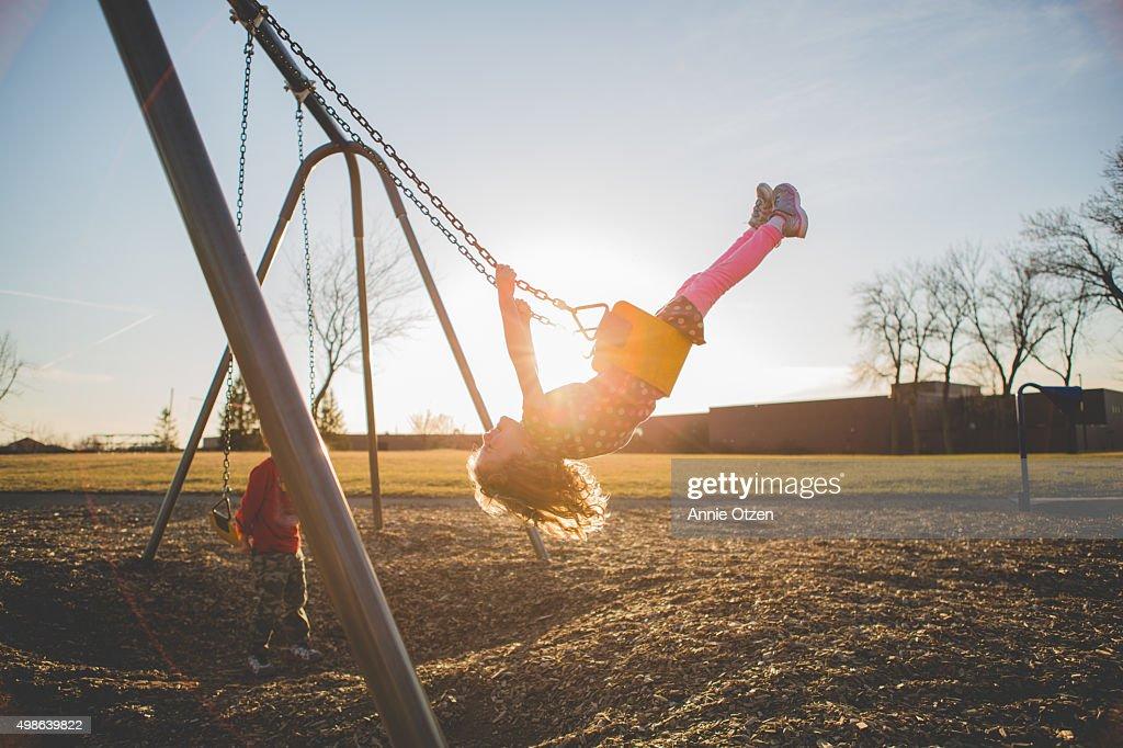 Children playing on a swing set : Foto de stock