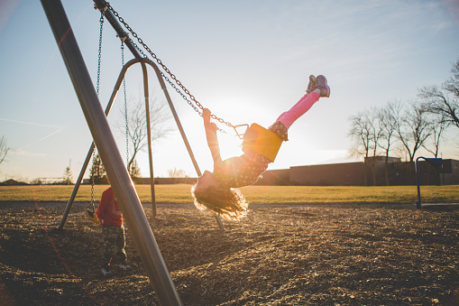 Children playing on a swing set - gettyimageskorea