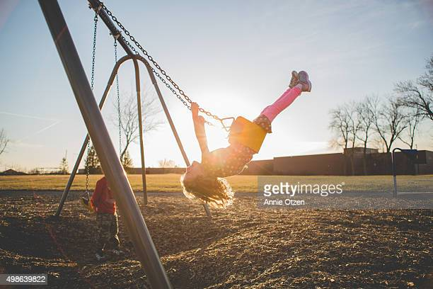 children playing on a swing set - playing stock pictures, royalty-free photos & images