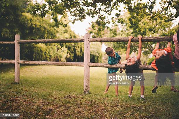 Children playing on a wooden fence in a summer park