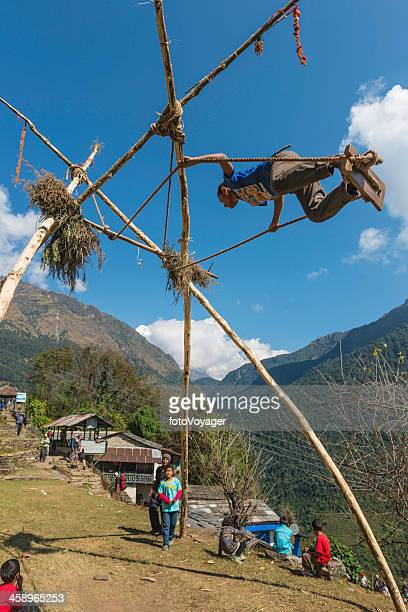 children playing on bamboo swing dasain festival himalayas nepal - dashain stock photos and pictures