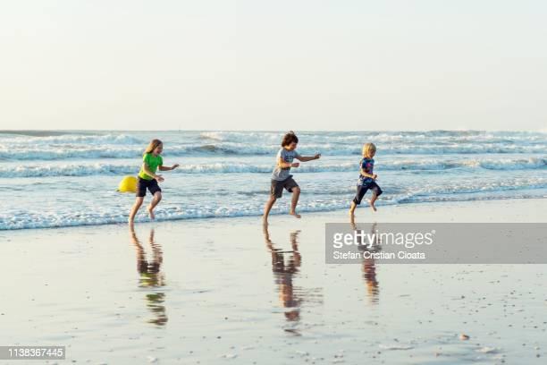 children playing on beach bredene aan zee belgium - noordzee stockfoto's en -beelden