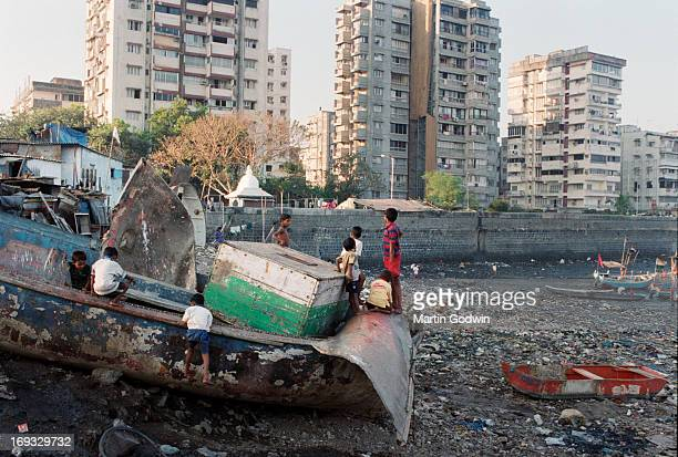 Children playing on broken boat on the edge of the Mumbai slum where it meets the beach used as a rubbish dumping ground and as a toilet with boats...