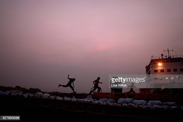 Children playing on on the banks of the Padma river where trucks carrying rice jute sugar cane and fish from the west and southwest of the country...