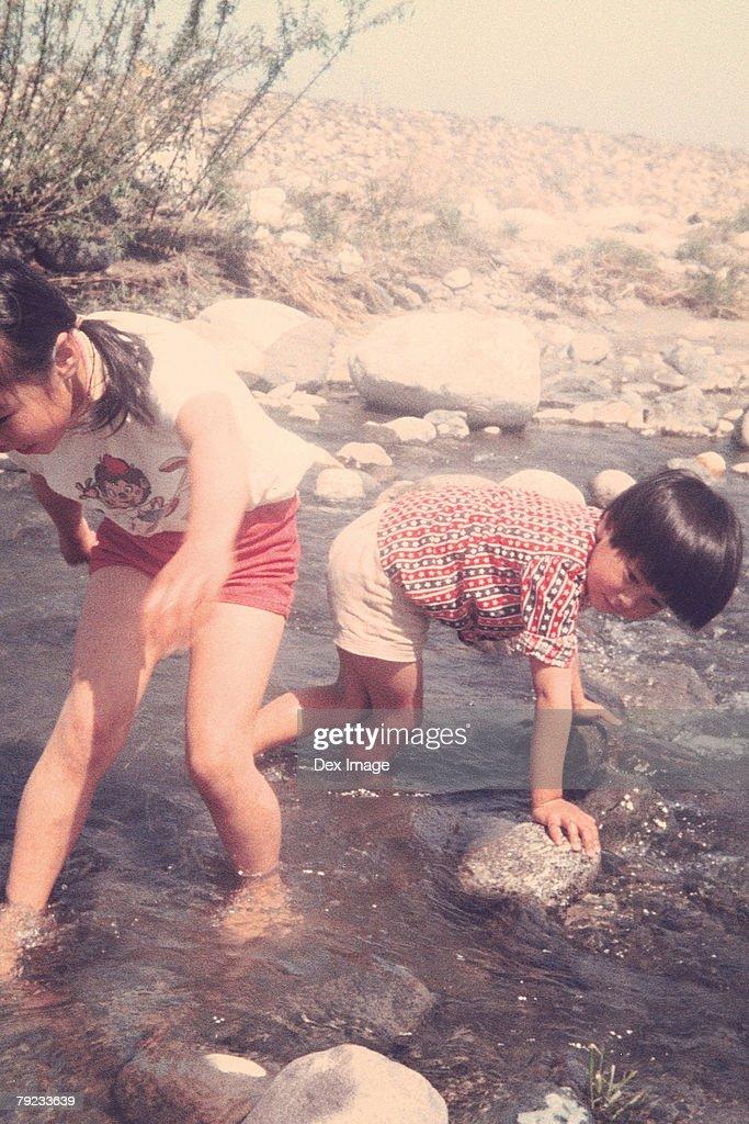 Children playing on riverbank : Stock Photo