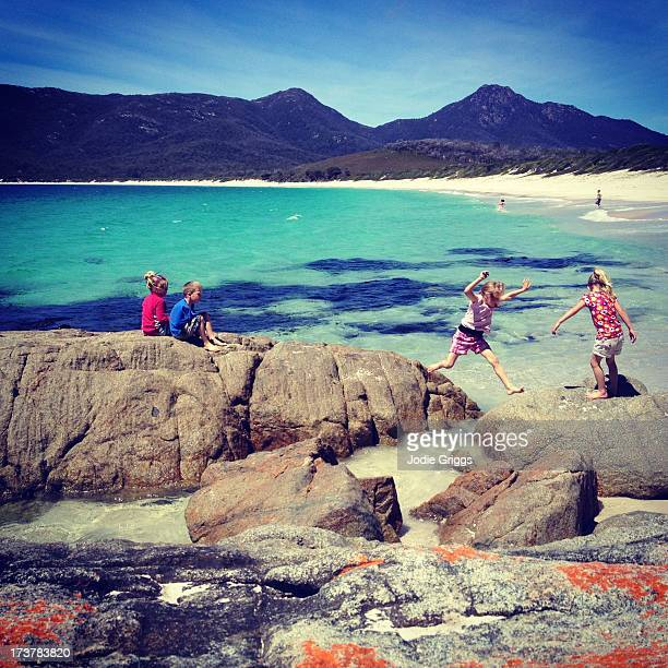 Children playing on rocks at the beach