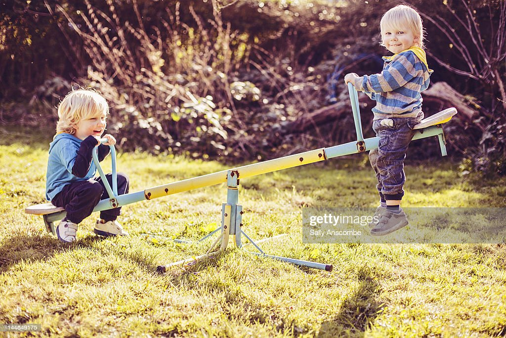 Children playing on seesaw : Stock Photo