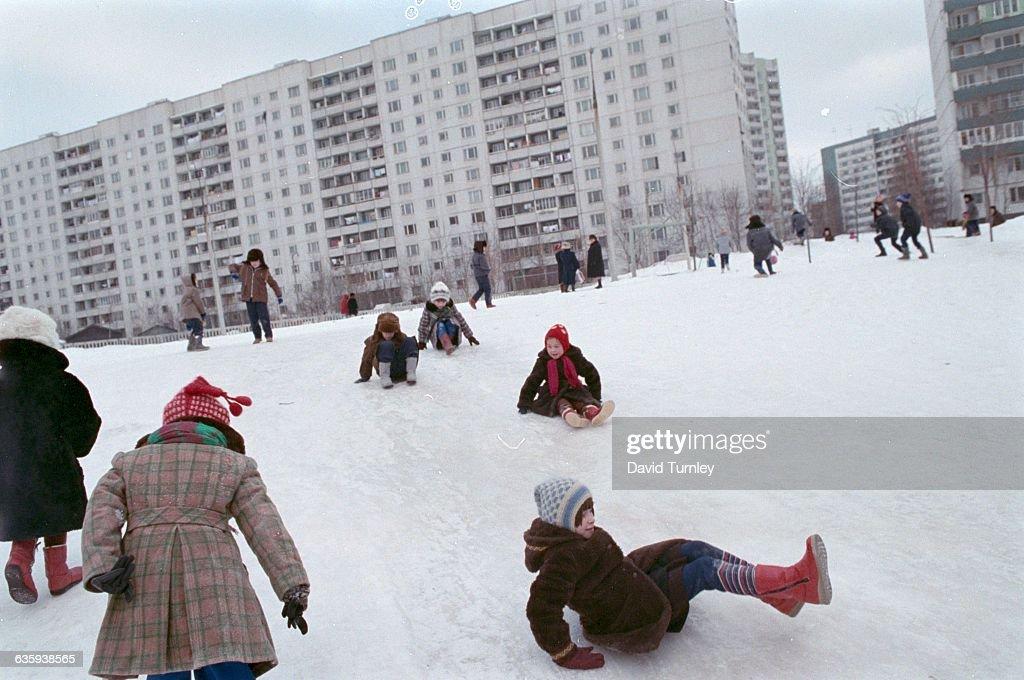 Children Playing on Snowy Hillside : News Photo