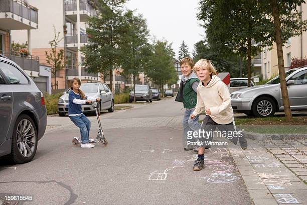 children playing on suburban street - stadtviertel stock-fotos und bilder