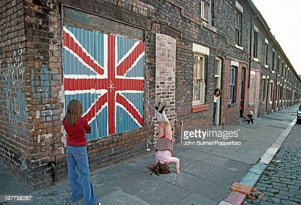 Children playing on the pavement of a terraced street in Manchester England in 1976