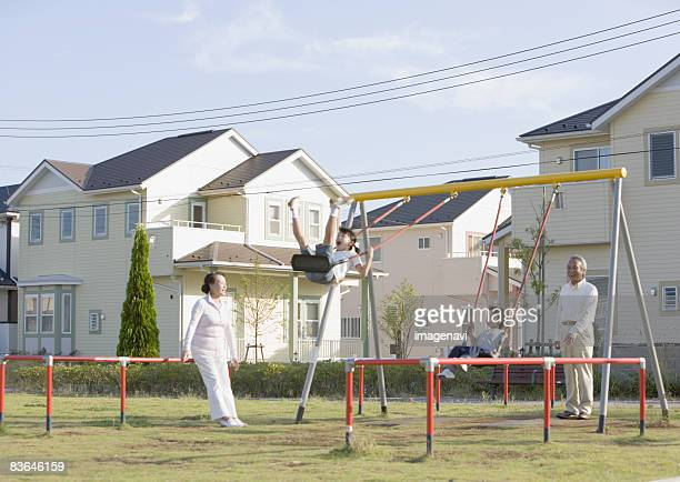 Children playing on the swing with their grandparents