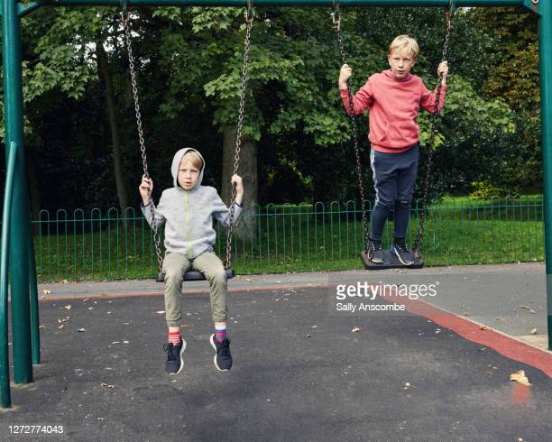children playing on the swings - leisure equipment stock pictures, royalty-free photos & images