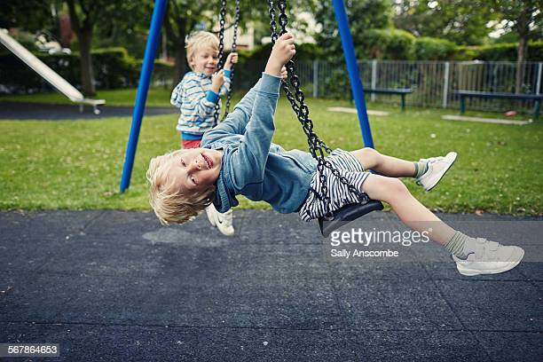 children playing on the swings - britain playgrounds stock pictures, royalty-free photos & images