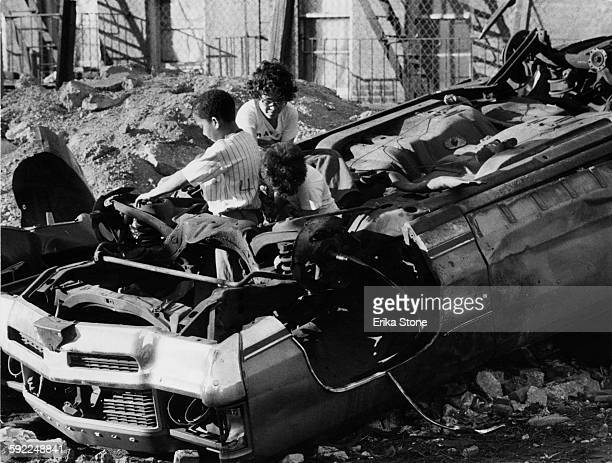 Children playing on the wreckage of a car on a patch of wasteground in East Harlem New York City USA circa 1979