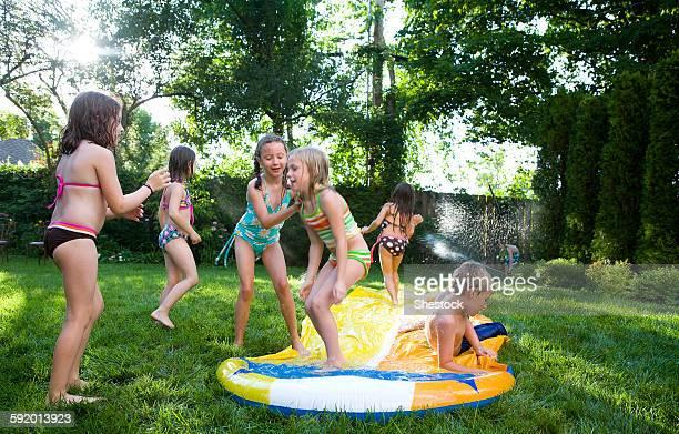 Children playing on water slide in backyard