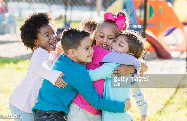 children playing outdoors on playground, hugging - children only stock pictures, royalty-free photos & images