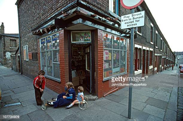 Children playing outside a corner shop at the end of a terraced street in Manchester England in 1976