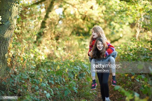 children playing piggyback rides - outdoors stock pictures, royalty-free photos & images